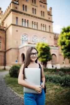Het portret van jonge aziatische studente die laptop of een tablet in slim en gelukkig gebruiken stelt bij universiteit of hogeschool