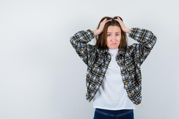 Het portret van jonge dame die het hoofd omklemt met dient t-shirt, jasje in en kijkt verbijsterd vooraanzicht
