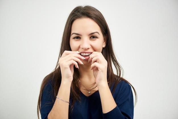Het portret van jonge donkerbruine vrouw flosst haar tanden met tandzijde