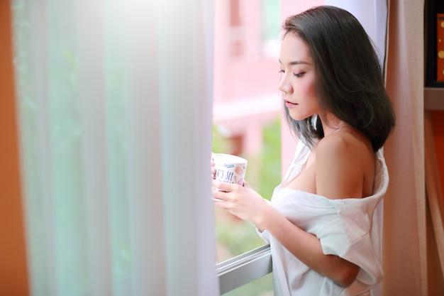 Het portret van jonge en sexy vrouw wordt wakker en ziet mening van slaapkamervenster