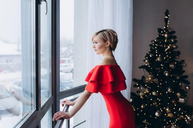 Het portret van jonge gelukkige vrolijke sexy vrouw in rode kleding dichtbij venster dient kerstmis verfraaid huis in. kerstmis, geluk, schoonheid, presenteert concept