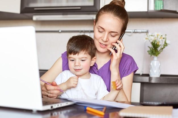 Het portret van jonge moeder werkt freelance aan laptop computer