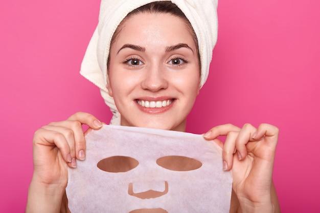Het portret van jonge mooie dame met perfecte huid die voedend gezichtsmasker, tijd aan kuuroordprocedures zet, kijkt gelukkig en ontspannen