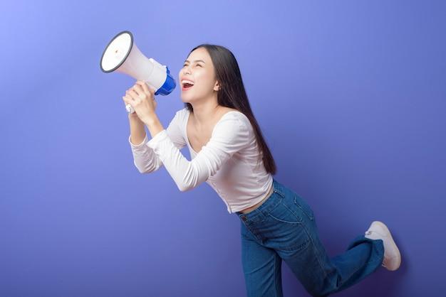 Het portret van jonge mooie glimlachende vrouw gebruikt megafoon om over geïsoleerde purpere studio aan te kondigen