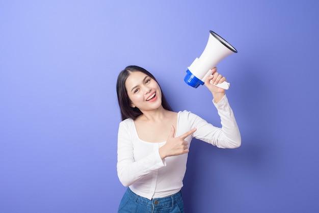 Het portret van jonge mooie glimlachende vrouw gebruikt megafoon om over geïsoleerde purple aan te kondigen