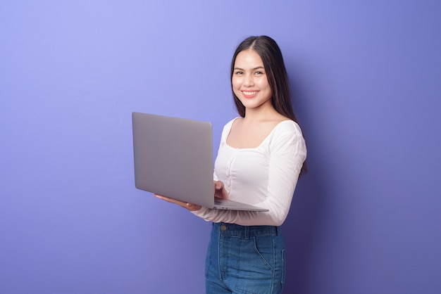 Het portret van jonge mooie glimlachende vrouw houdt laptop over geïsoleerde purple