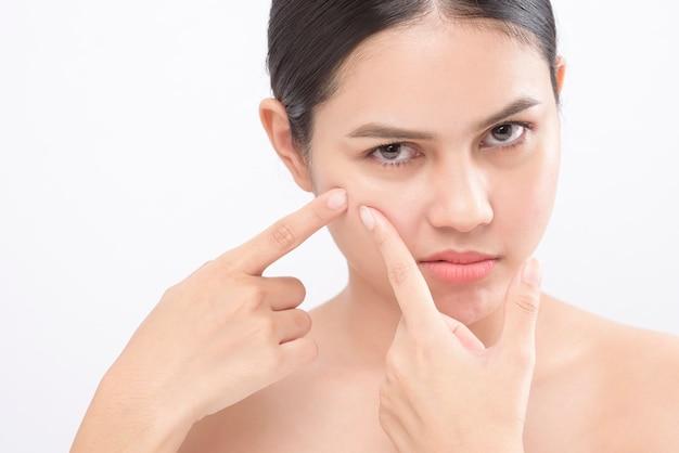Het portret van jonge mooie vrouw controleert haar huid en knalt pukkel over wit