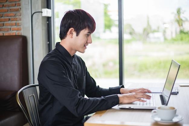 Het portret van jonge toevallige zakenman neemt een onderbreking en zit in het koffie en werkt aan zijn laptop