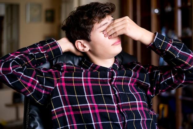Het portret van jonge vermoeide jongen ontspant thuis in leunstoel thuis huiswerk f