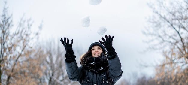 Het portret van jonge vrouw jongleert in openlucht met sneeuwballen op een de winter sneeuwdag