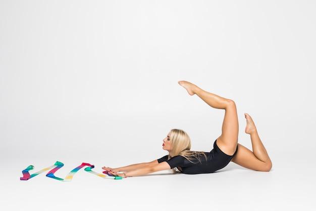 Het portret van jonge vrouwenturner die calilisthenicsoefening met lint opleiden. art gymnastiek concept.