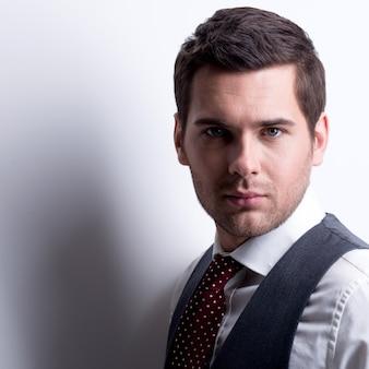 Het portret van jonge zakenman in grijs kostuum stelt over muur met contrastschaduwen.