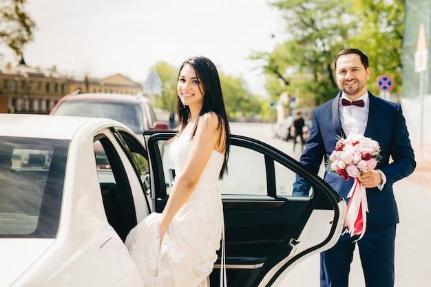 Het portret van jonggehuwdepaar zit in auto na ceremonie, heeft gelukkige uitdrukking