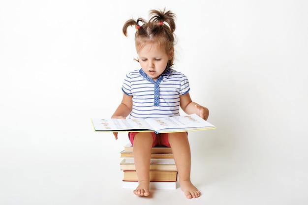 Het portret van klein aanbiddelijk kind zit op stapel boeken, houdt interessant boek, bekijkt beelden, probeert sommige woorden te lezen, treft voorbereidingen voor school, geïsoleerd op wit. slim meisje