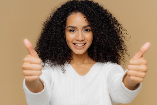 Het portret van knap wijfje heft duimen op, toont als gebaar in camera, geniet van aardige presentatie