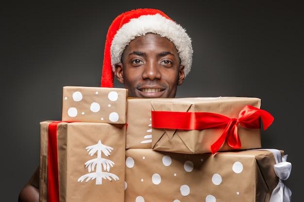 Het portret van knappe jonge zwarte lachende man in kerstmuts met geschenken op donker.