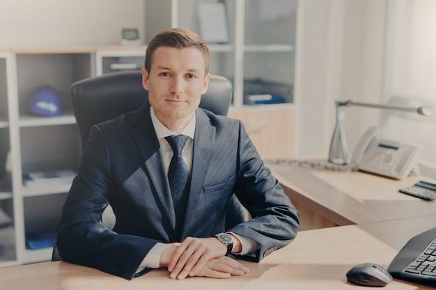 Het portret van knappe welvarende mannelijke manager zit bij kabinet, kijkt direct in camera