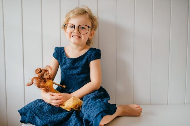 Het portret van leuk en grappig meisje in glazen houdt haar mooie barbie en het stellen over witte muur