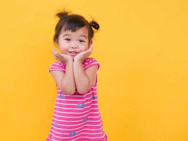 Het portret van leuk meisje glimlacht over gele achtergrond.