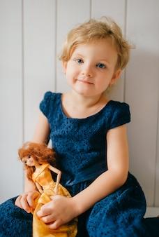 Het portret van leuk meisje houdt haar mooie barbie en het stellen over witte muur