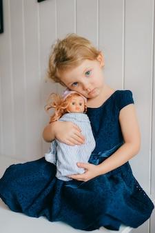 Het portret van leuk meisje houdt haar mooie barbie, zit in heldere babyruimte, kijkt opzij