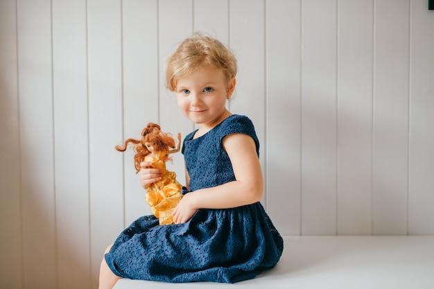 Het portret van leuk meisje houdt haar mooie barbie, zit in heldere babyruimte