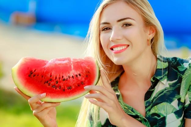 Het portret van leuk meisje maakt grappig gezicht en glimlach met watermeloenplakken. mooie vrouw die rijpe watermeloen eet. concept fruit, vers, gezond voedsel, veganistisch, vitamines, dieet
