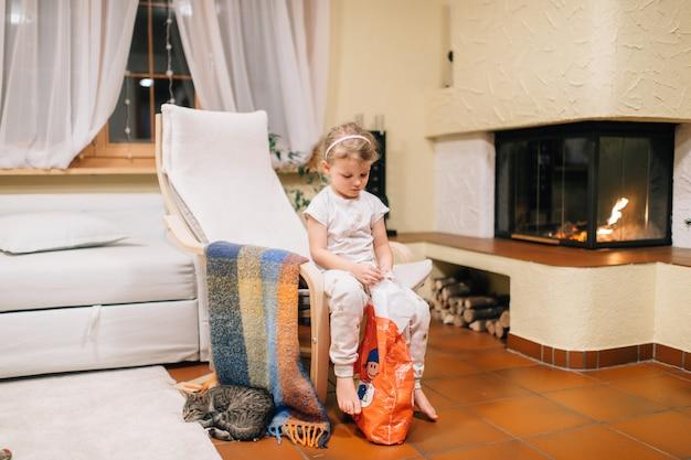 Het portret van leuk meisje zit in haar ruimte zit bij stoel met slapend katje naast