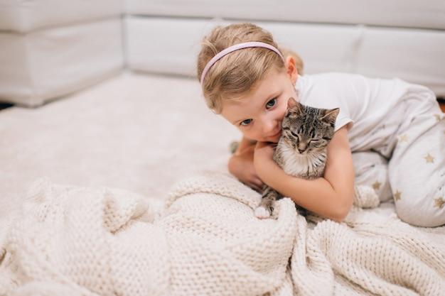 Het portret van leuk meisje zit in haar ruimte zit op een vloer met mooie kat bij