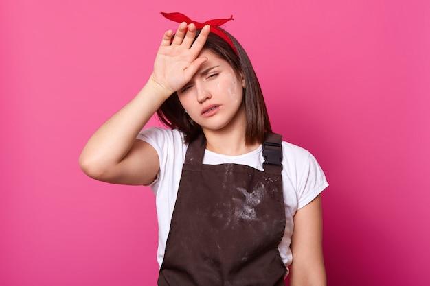 Het portret van meisje in bruine schort, witte t-shirt, rode haarband, met vermoeide uitdrukking op geïsoleerd nam toe. model poseert in fotostudio met half geopende ogen, houdt hand op voorhoofd.
