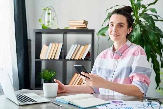 Het portret van moderne jonge vrouw die camera bekijken en smartphone houden terwijl thuis het werken, kopieert ruimte