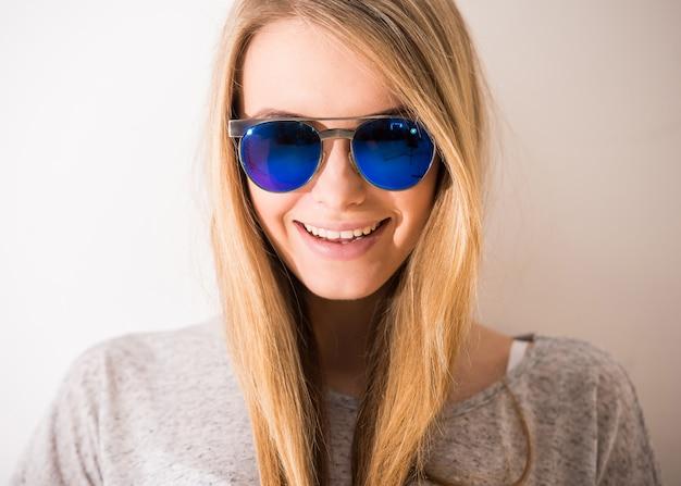 Het portret van mooi blondemeisje met zonnebril glimlacht