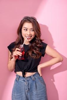 Het portret van mooi gelukkig leuk vrouwenmeisje in vrijetijdskleding drinkt rood sodawater uit fles met stro over roze muur