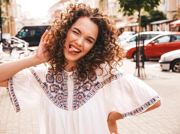 Het portret van mooi het glimlachen model met het kapsel van afrokrullen kleedde zich in de zomer hipster witte kleding.