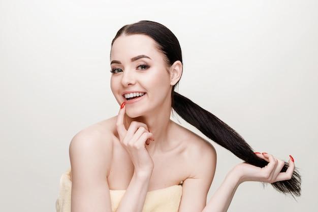 Het portret van mooi jong model met natuurlijk naakt maakt omhoog op grijs