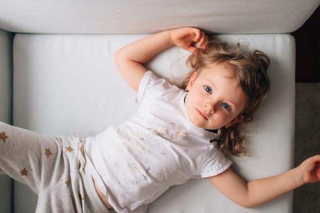 Het portret van mooi meisje ligt op haar wit bed