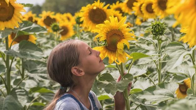 Het portret van mooi preteen meisje met lang haar op een zonnebloemgebied van zonnebloemen