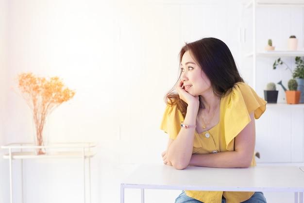 Het portret van mooie aziatische vrouw rust haar scheenbeen aan één hand met glimlachgezicht en kijkt uit venster met exemplaarruimte.