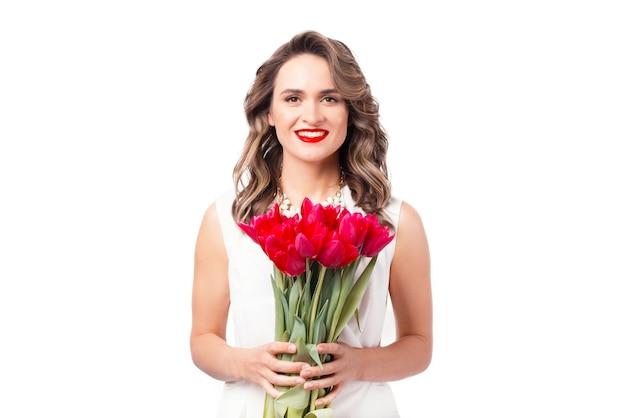 Het portret van mooie glimlachende vrouw kleedde zich in wit holdingsboeket van roze tulpen