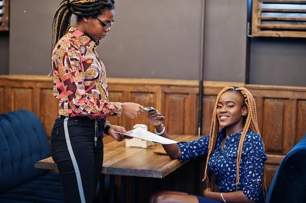 Het portret van mooie jonge afrikaanse bedrijfsvrouw, draagt op blauwe blouse en rok, zittend bij restaurant en geeft creditcard aan het meisje van kelnersafro.