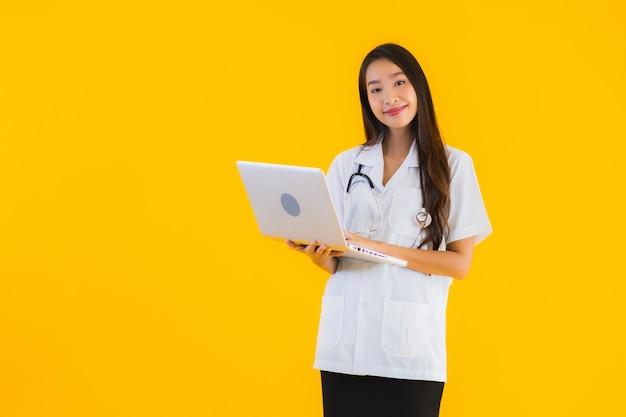 Het portret van mooie jonge aziatische artsenvrouw gebruikt laptop