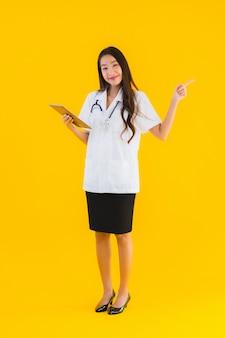 Het portret van mooie jonge aziatische artsenvrouw gebruikt slim tabletapparaat
