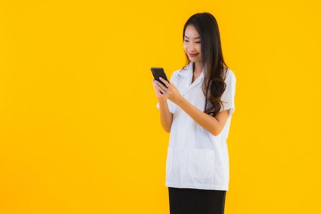 Het portret van mooie jonge aziatische artsenvrouw gebruikt smartphone