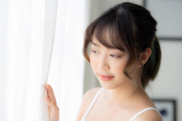 Het portret van mooie jonge aziatische vrouw status bekijkt het venster