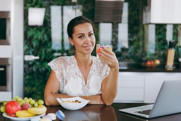 Het portret van mooie jonge vrouw die met laptop werkt tijdens het ontbijt met ontbijtgranen en melk en sinaasappelsap drinkt drinking