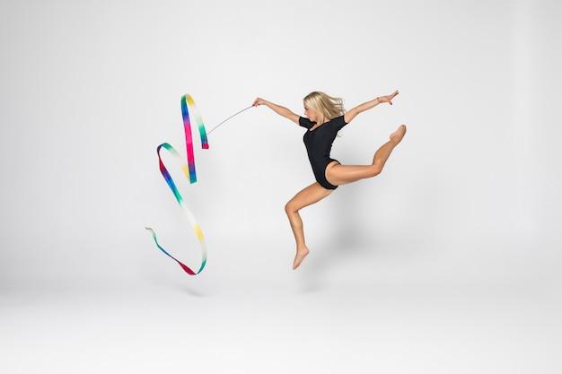 Het portret van mooie jonge vrouwenturner die calilisthenicsoefening met lint opleiden. art gymnastiek concept.