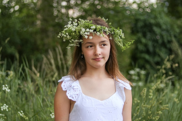 Het portret van mooie romantisch preteen meisje met groene en witte verse bloemenkroon op hoofd in openlucht.