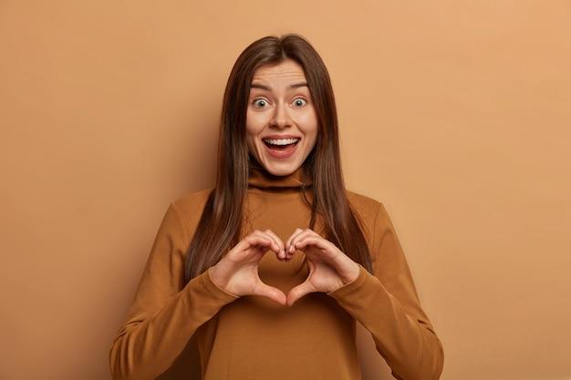 Het portret van mooie vrolijke vrouw vormt hartgebaar over borst, betuigt liefde en medeleven aan vriend, heeft grappige uitdrukking