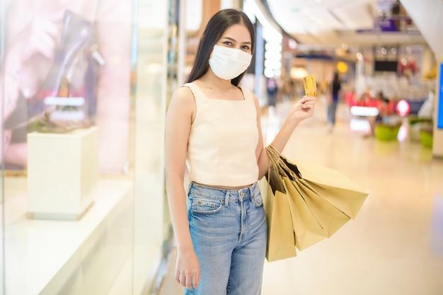 Het portret van mooie vrouw draagt gezichtsmasker in winkelcentrum
