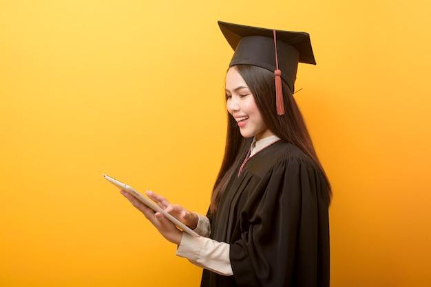 Het portret van mooie vrouw in graduatietoga houdt tablet op gele achtergrond